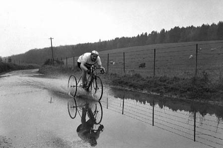 Norman Wiles cycles through flooded road